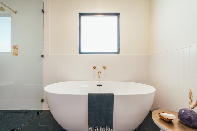 white freestanding tub with gray towel draped over, gold wall-mounted faucet and handles, white wall tile on half of the bathroom wall, small table with bathroom accessories, gray floor tile, glass shower door