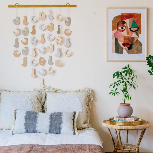 room showing bed, hanging wall art, side table with plant, and art print by Justina Blakeney
