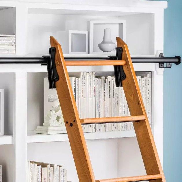 Wooden sliding library ladder on black pole