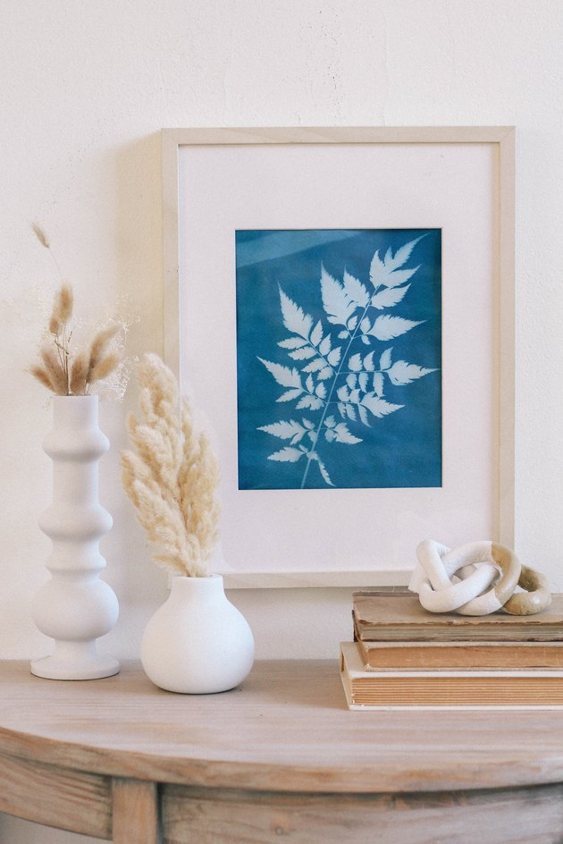Framed blue sun print hung on wall above table with white vases, dried flowers, books and a ceramic knot