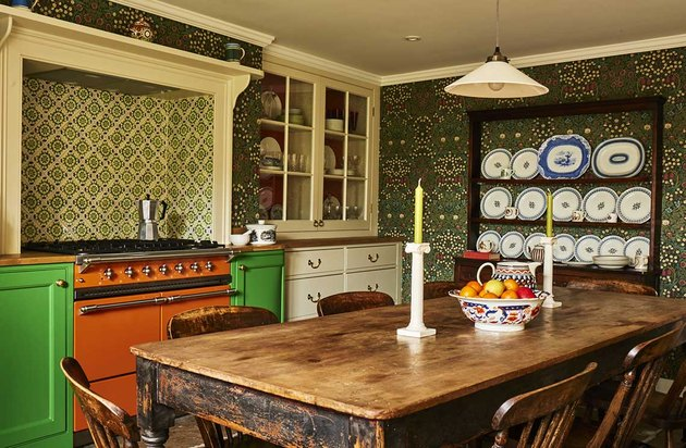arts and crafts kitchen with wallpaper and orange stove
