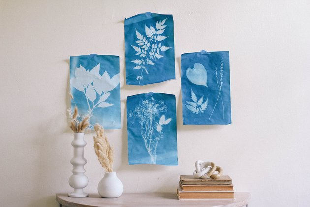 Four blue sun prints hung on wall with tape above table with white vases and books