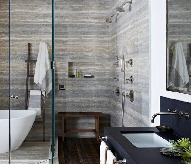 rustic shower tile in bathroom with white tub and drop-in sink