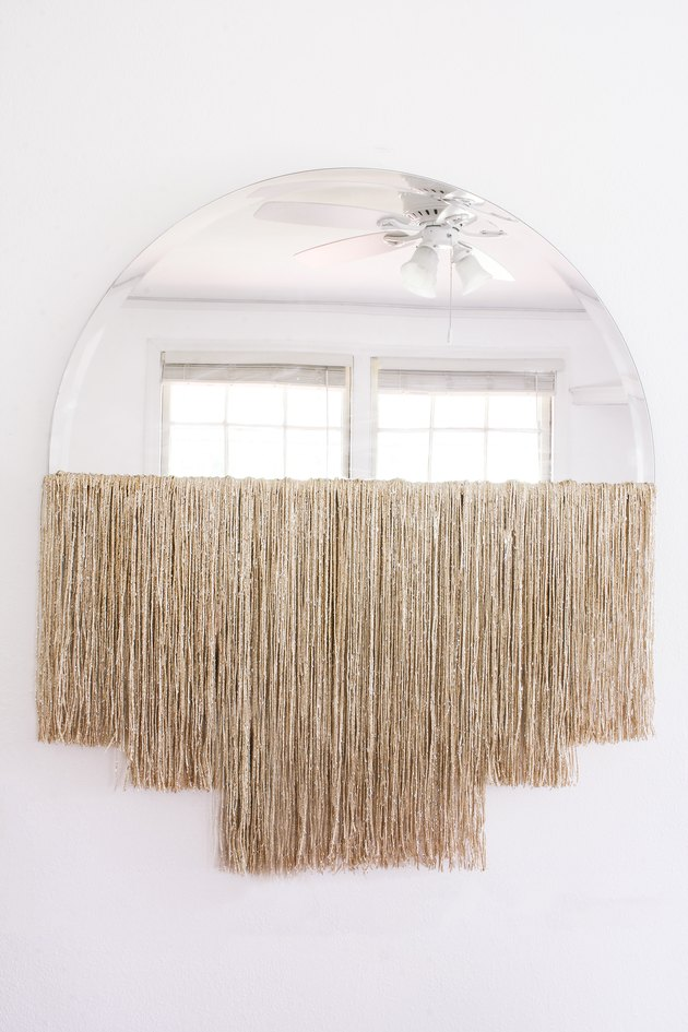 DIY fringe mirror hanging on wall