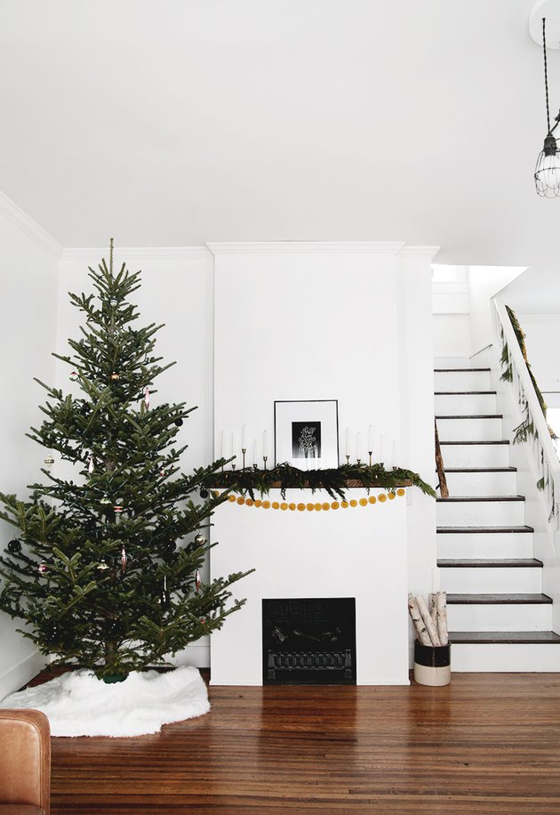 white living room with Scandinavian Christmas tree  and fireplace