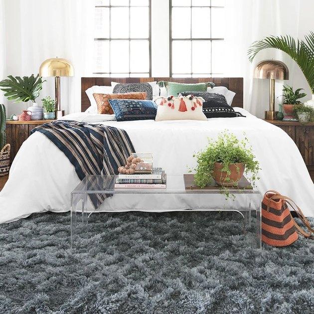 chambre avec literie et rideaux blancs et tapis à poils longs gris