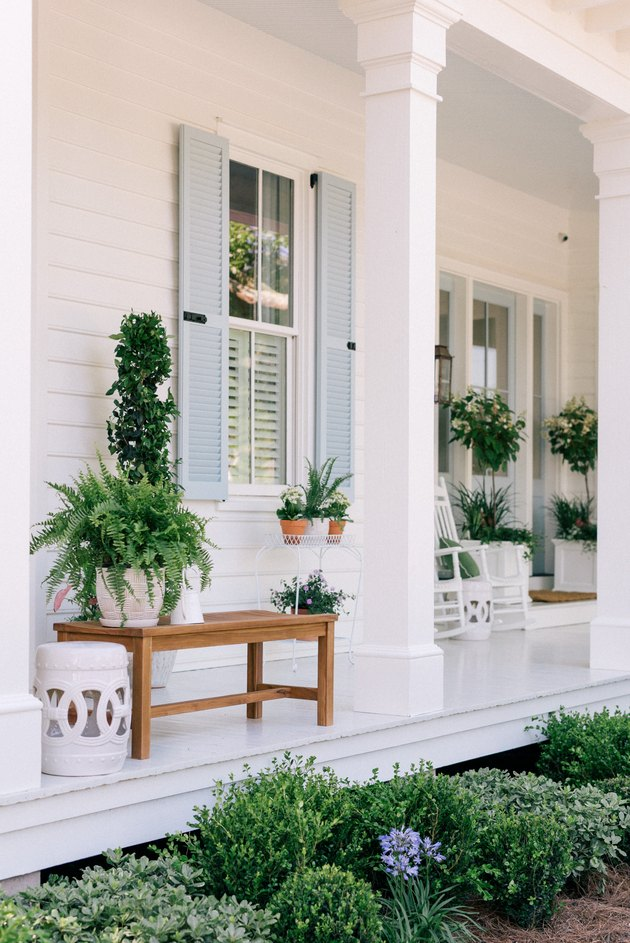 Blue exterior house shutters shown on white front porch with potted plants