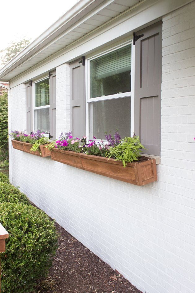 Gray exterior house shutters with cedar flower boxes