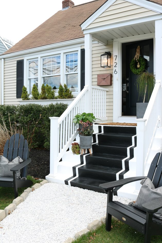 Black exterior house shutters with black and white painted steps and black front door