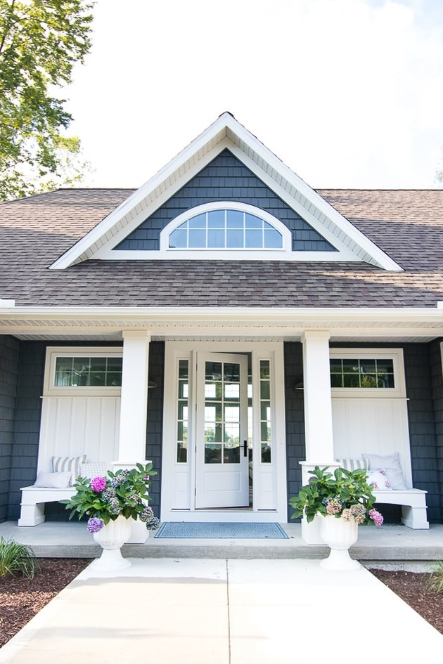 Charcoal and white farmhouse exterior colors with front porch and potted plants
