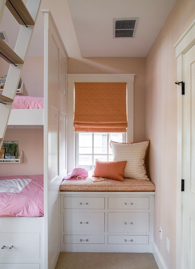attic storage in girls bedroom with orange Roman shade and window seat