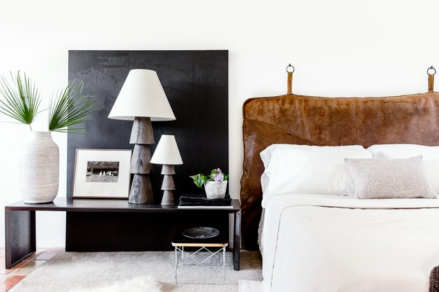 Minimalist bedroom with leather headboard behind bed
