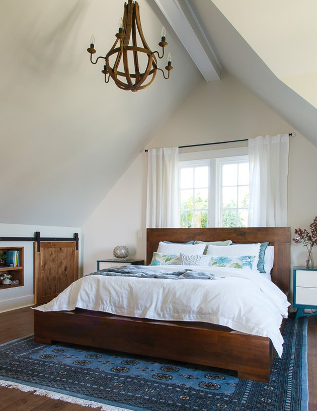 attic storage in bedroom with midcentury bed and sliding barn door