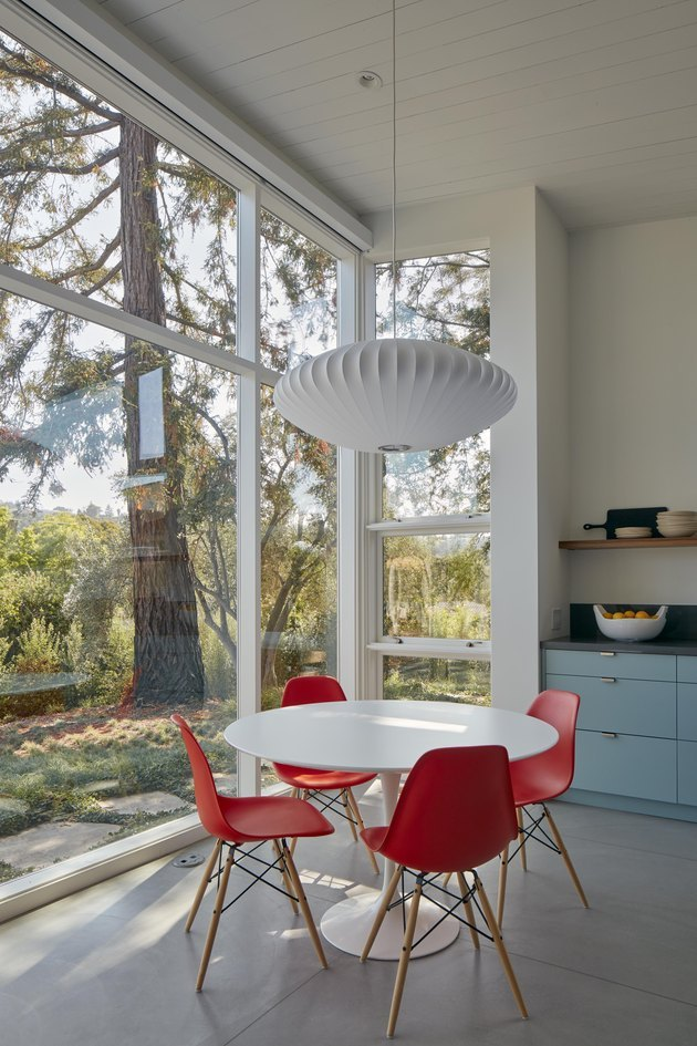 midcentury-style dining room with large windows looking out to redwoods