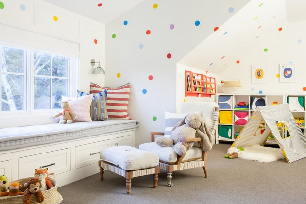Attic playroom with polka dot walls, window seat, and tent
