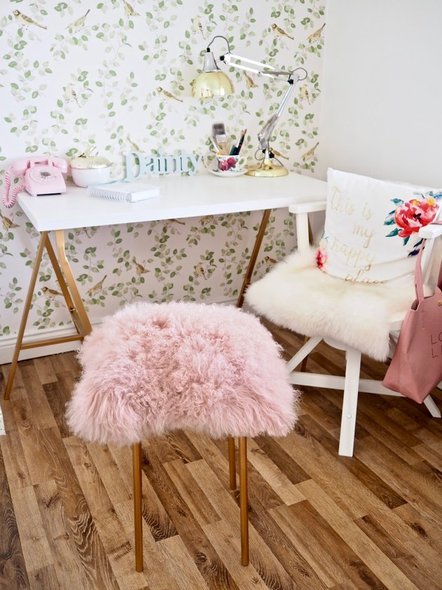 A pink furry stool in front of a desk.