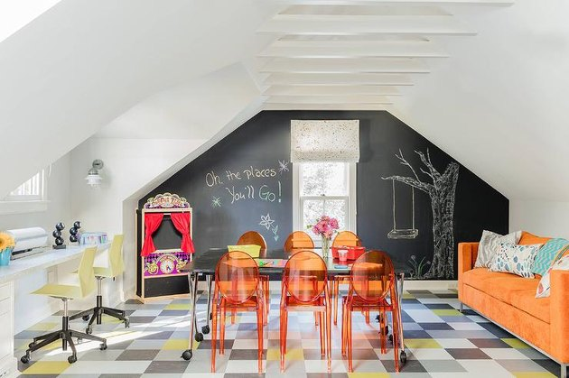 attic playroom with chalkboard wall, orange chairs, and orange sofa