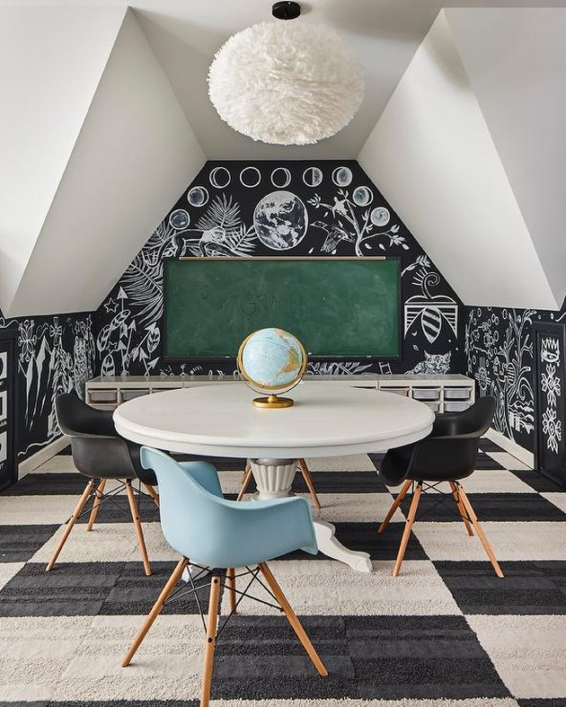attic game room with black and white checkered rub, chalkboard walls, green chalkboard, round white tale, mid century modern chairs, globe, coral pendant lamp.