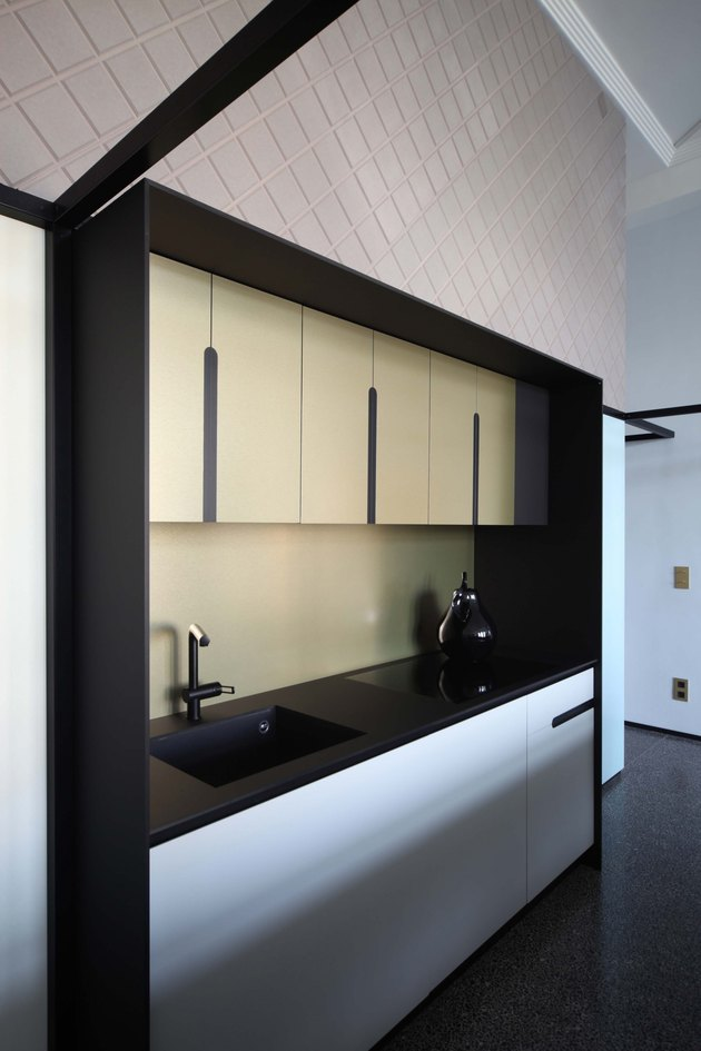 sleek kitchen with black countertops and yellow cabinets