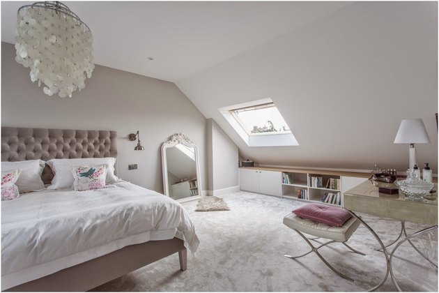 attic storage in bedroom with low storage unit and capiz shell chandelier