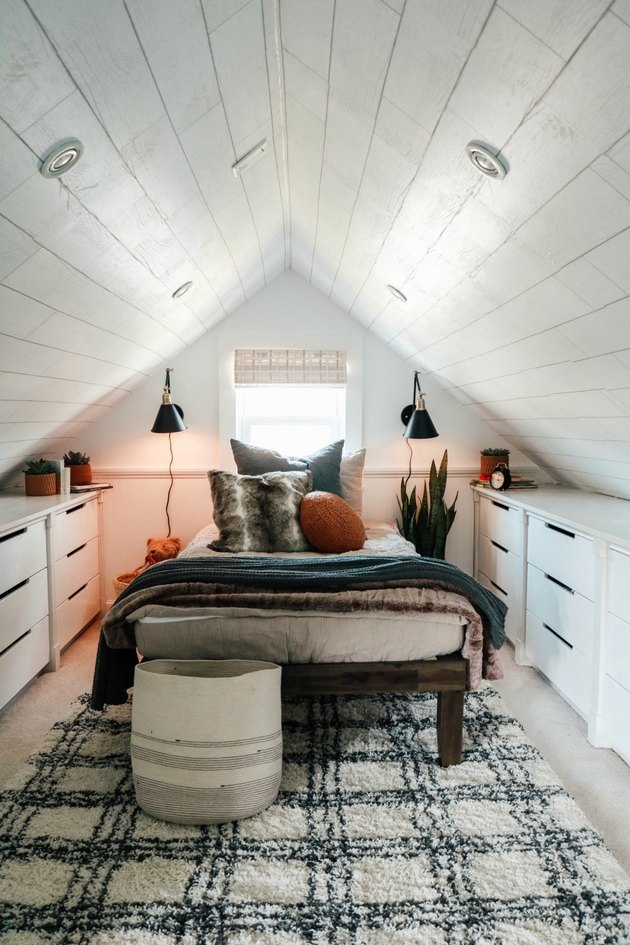 Attic bedroom idea with plaid area rug and storage dressers
