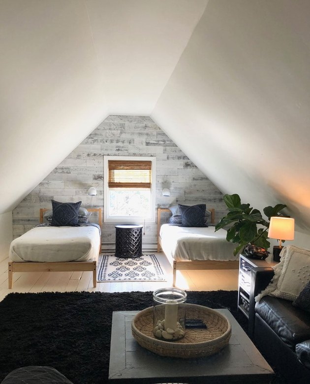 Attic bedroom idea with twin beds and peel-and-stick wallpaper accent wall