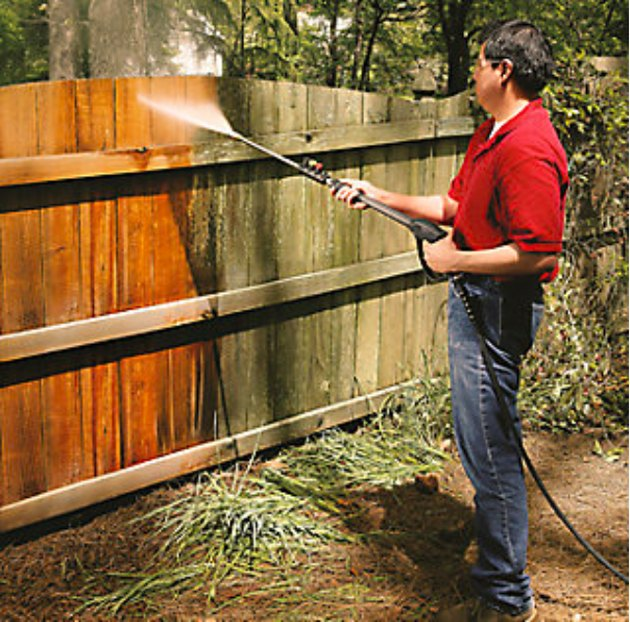 Pressure washing a fence.