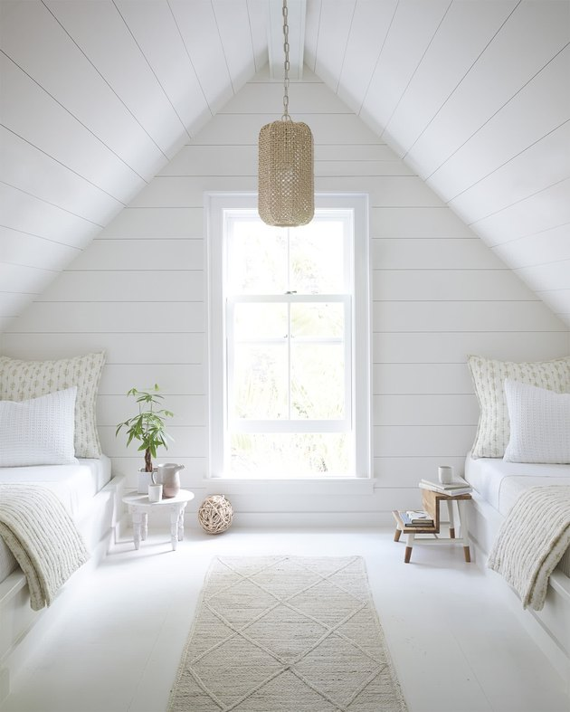 Attic bedroom idea with white shiplap walls and ceiling and twin beds