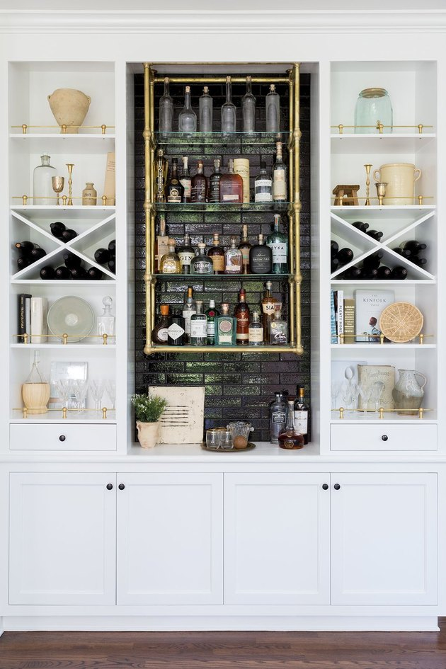 white industrial bar idea with black brick center and brass pipe shelves