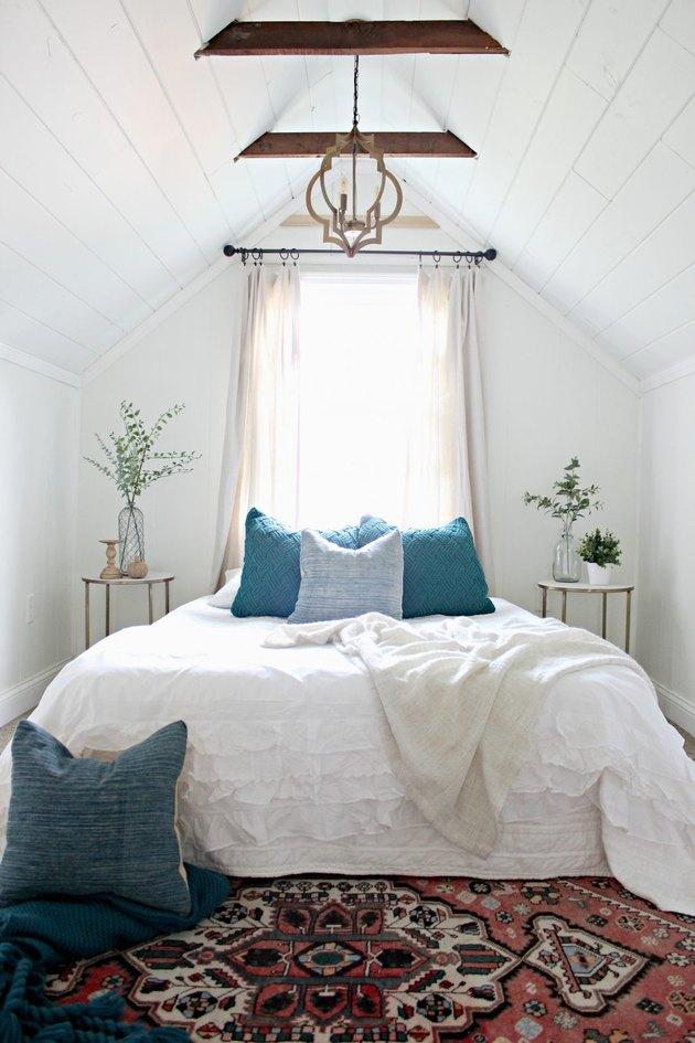 Attic bedroom idea with white bed linens and vintage patterned rug