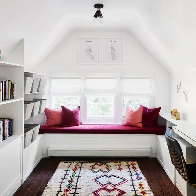 small attic library with pink window seat and pillows