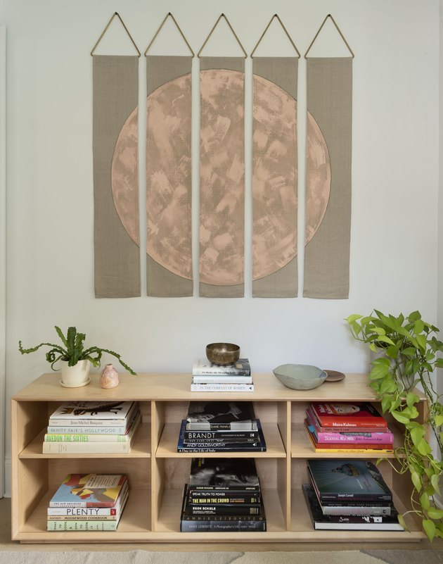 Artwork over wood shelving unit with books