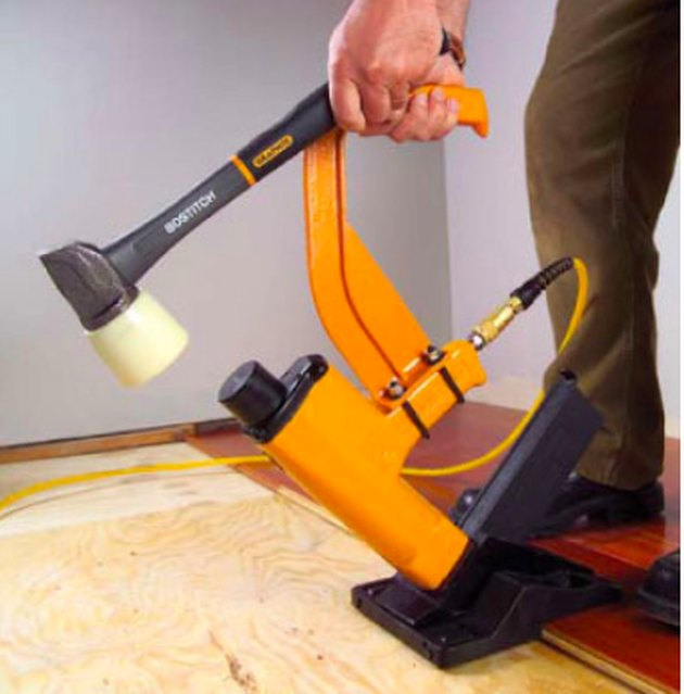 Man installing flooring with a nailer.
