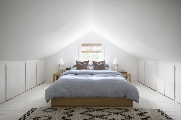 Small attic ideas for white painted walls and a minimalist oak-framed bed.