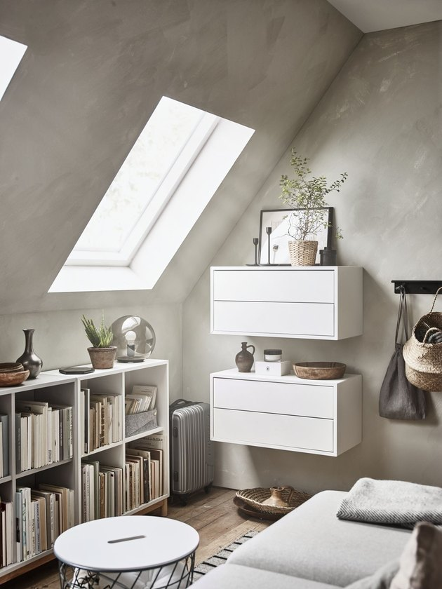 small attic library with gray walls and white bookcases and storage