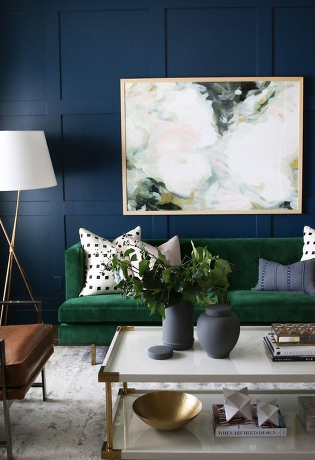 navy blue living room idea with velvet green sofa filled with accent pillows