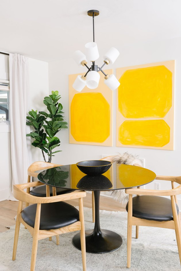 Dining room with mustard yellow abstract artwork on wall next to small dining table and chairs