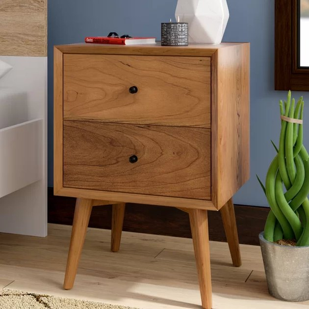 Mid-century nightstand with long legs, two drawers, and medium finish