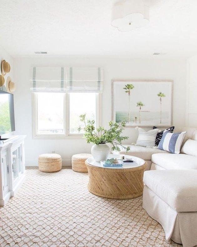 salon côtier avec tapis de jute, sectionnel blanc cassé, poufs en osier, stores blancs, murs blancs, plantes, art.