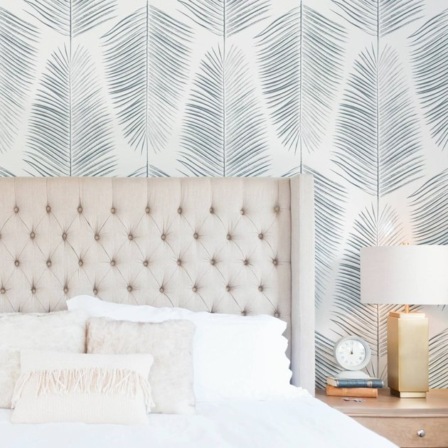 coastal wallpaper in coastal bedroom with palm print wallpaper
