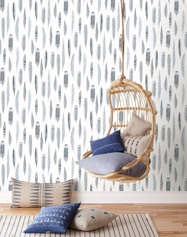 rattan hanging chair against blue and white feather coastal wallpaper