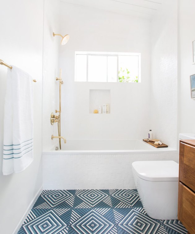 white coastal bathrooms with blue geometric concrete tile floor, brass fixtures and natural wood vanity.