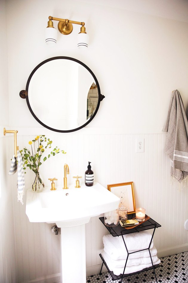 bathroom pedestal sink with round mirror above and black and white mosaic floor tile