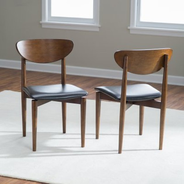 Dark wooden mid-century dining chairs, armless with black leather seat