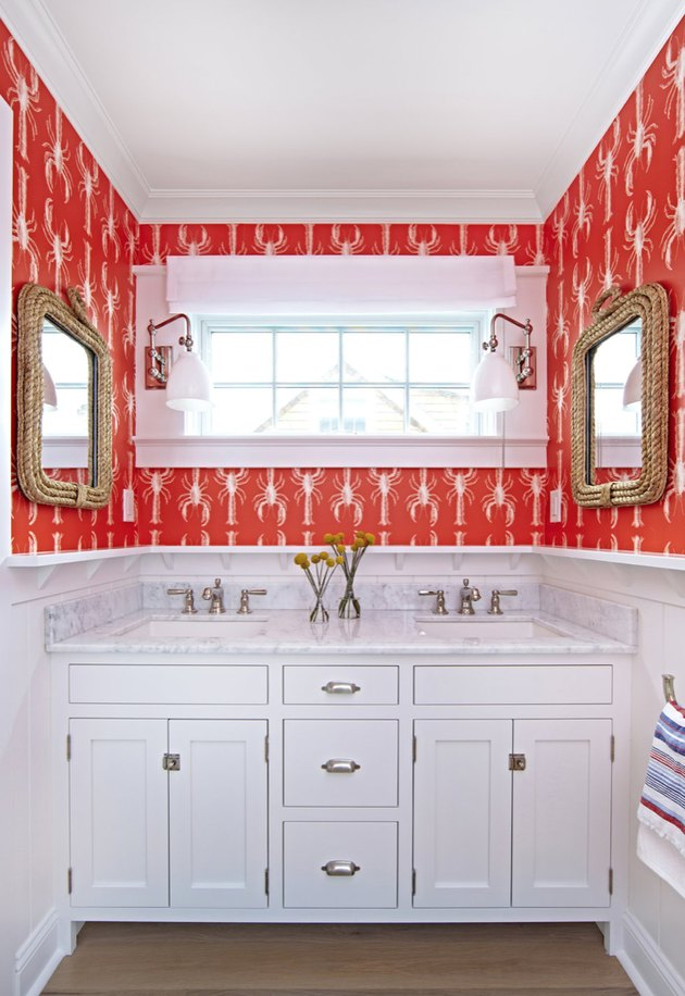 Marble coastal bathrooms with his and her sinks with red lobster patterned wallpaper and rope frame mirrors.