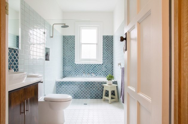 coastal bathrooms with blue scallop tile bathtub, shower and backsplash with dark wood vanity and white tile floors.