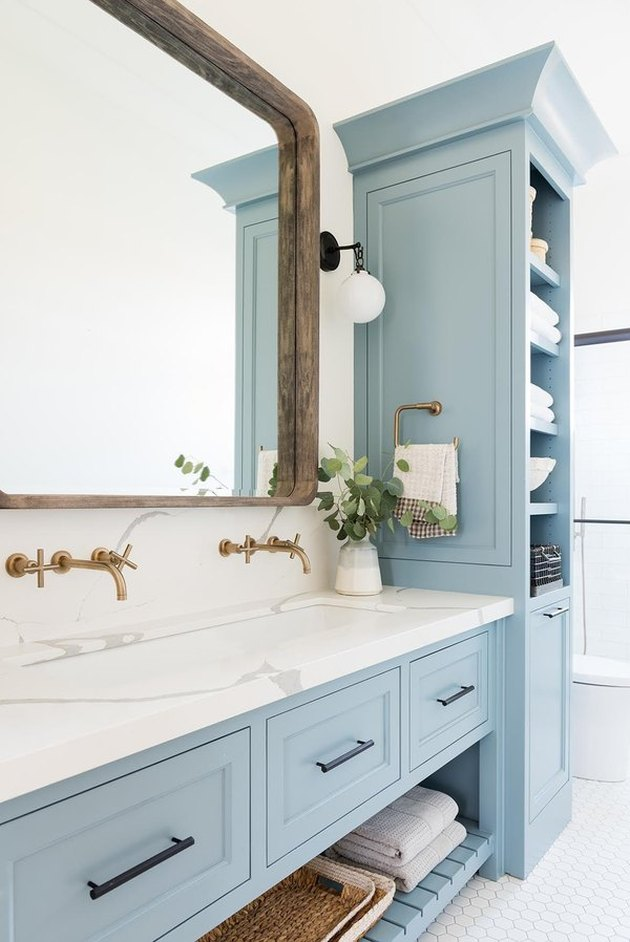 coastal bathrooms with large farmhouse mirror, marble vanity, brass faucets, blue cabinets and shelves.