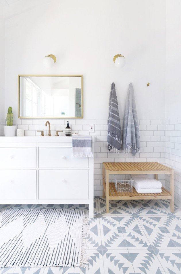 coastal bathrooms with geometric floor tile, subway tile, white vanity, brass mirror and sconces, turkish towels, natural wood towel rack.