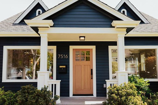 craftsman bungalow with blue home exterior in navy with white accents and natural door