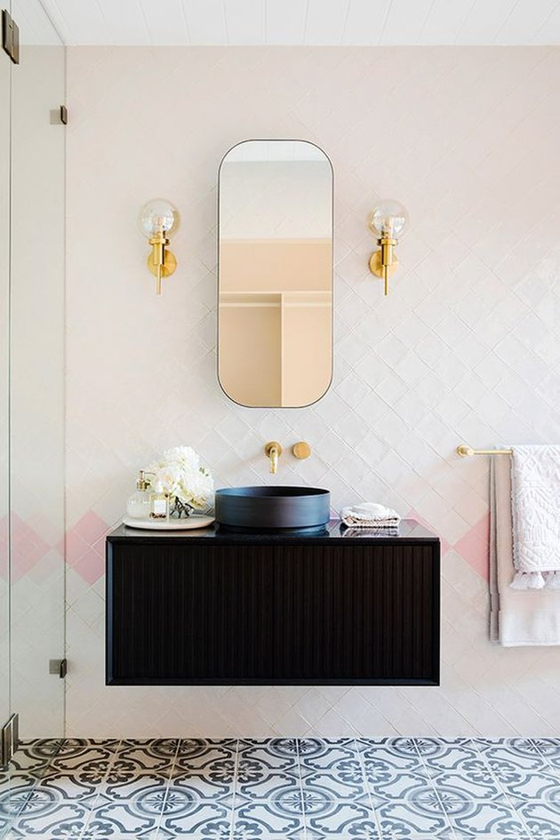 pink bathroom lighting idea with black vanity and glass wall lights